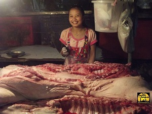 Cute girl with a knife and cutting some pig at KlongToey Market