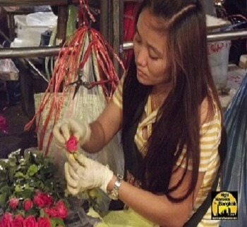 Pretty Thai girl wrking with some roses at the Flower Market in Bangkok